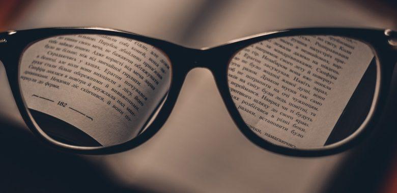 eine Brille auf einem aufgeklappten Buch