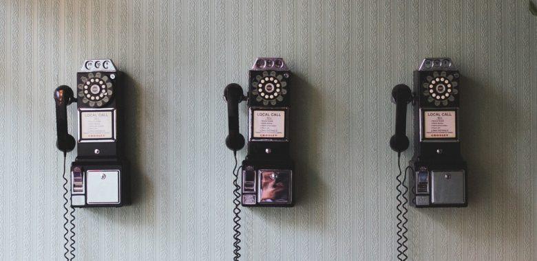 drei alte Telefone mit Wählscheibe hängen an der Wand
